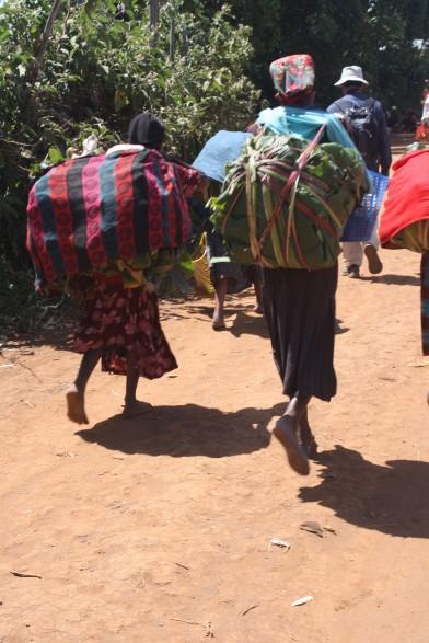 Vrouwen lopen naar de markt met tassen vol groente, om te verkopen.